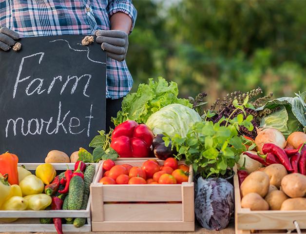 "Chalkboard that says ""Farm market"" behind fresh produce"